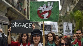 """Des manifestants brandissent diverses pancartes s'adressant àAbdelaziz Bouteflika, le 8 mars, à Alger. Le logo du film """"SOS Fantômes"""" fait référence au fait que les Algériens n'ont pas entendu la voix de leur président depuis octobre 2014. (RYAD KRAMDI / AFP)"""