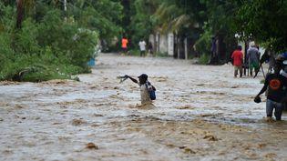 Des habitants d'Haïti tentent de traverser la rivière La Rouyonne dans la commune de Leogane, au sud de Port-au-Prince, le 5 octobre 2016. (HECTOR RETAMAL / AFP)