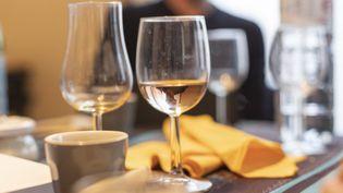 Des verres de vin sur la table d'un restaurant, à Paris, le 25 décembre 2019. (ANTOINE WDO / HANS LUCAS / AFP)