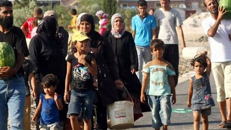 Des réfugiés syriens à proximité du camp de réfugiés de Kilis en Turquie. (ADEM ALTAN / AFP)