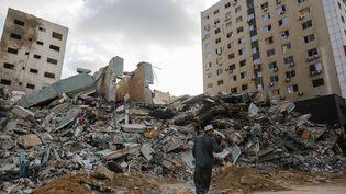 Un homme se tient devant l'immeuble détruit qui abritait les médias Associated Press et Al-Jazeera, le 16 mai 2021 à Gaza. (SAMEH RAHMI / AFP)
