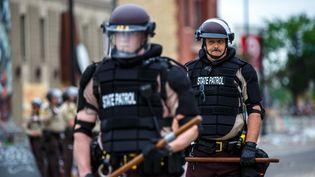 Des agents de la garde nationale américaine dans une rue de Minneapolis (Etats-Unis), le 29 mai 2020, face à des manifestants réclamant justice après la mort de George Floyd survenue à la suite de son arrestation par quatre policiers. (KEREM YUCEL / AFP)