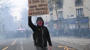 """Un manifestant masqué brandit une pancarte lors de la mobilisation contre la proposition de loi sur la """"sécurité globale"""" à Paris, le 5 décembre 2020. (ANNE-CHRISTINE POUJOULAT / AFP)"""