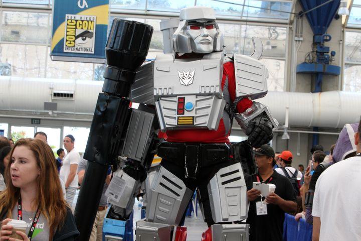 """Au Comic-Con 2016, un cosplayer en costume de """"Transformer"""" se promène dans les allées de la convention. (BILL WECHTER / AFP)"""