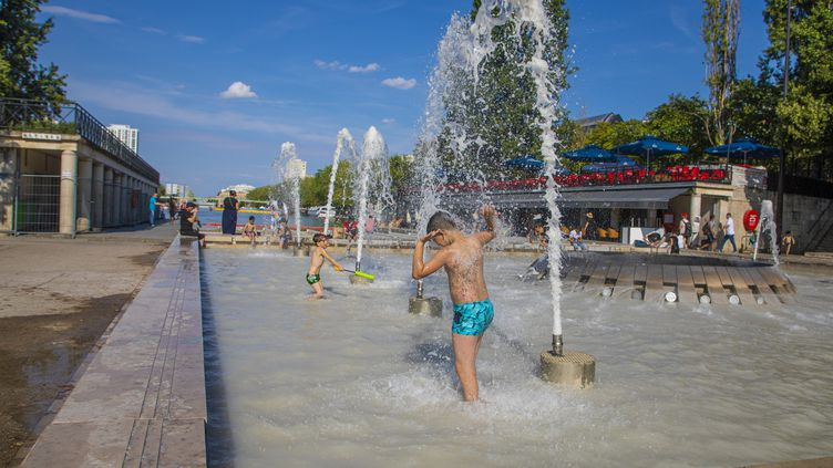 Des enfants se rafraîchissent dans une fontaine de la place de Stalingrad, à Paris, le 10 août 2020. (LP/YANN FOREIX / MAXPPP)