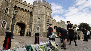 Des employés du château de Windsor, au Royaume-Uni, déposent des fleurs devant l'entrée après la mort du prince Philip, vendredi 9 avril 2021. (ADRIAN DENNIS / AFP)