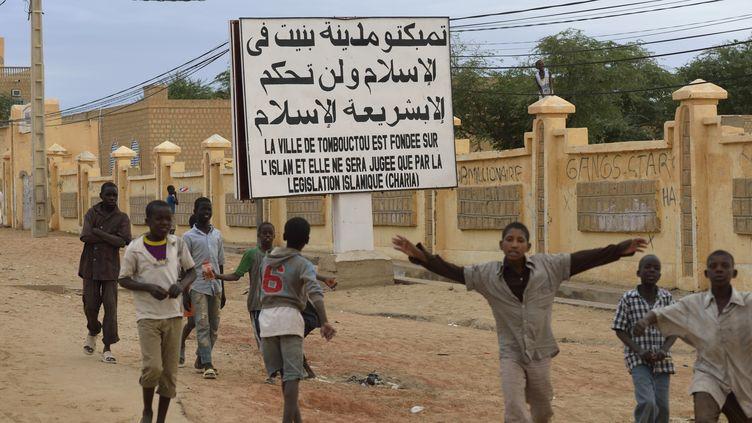 """Des enfants accueillent les troupes maliennes et françaises à Tombouctou (Mali) le 28 janvier 2013, devant un panneau qui prévient que """"la ville de Tombouctou est fondée sur l'islam et elle ne sera jugée que par la législation islamique (charia)"""". (ERIC FEFERBERG / AFP)"""