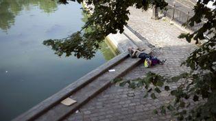 Un SDF se repose sur les bords du canal Saint-Martin, à Paris, le 10 septembre 2012. (FRED DUFOUR / AFP)