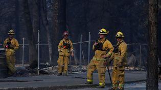 Des pompiers regardent le président américain, Donald Trump, en visite à Paradise, ville détruite par un incendie en Californie, le 17 novembre 2018. (LEAH MILLIS / REUTERS)