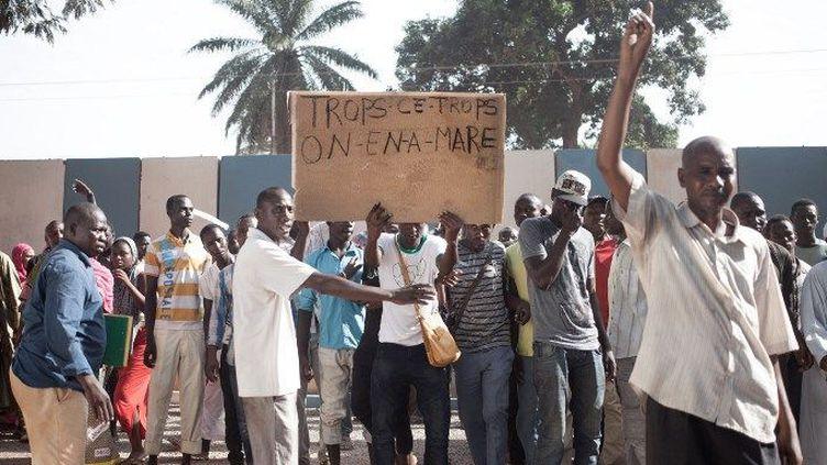 Un homme brandissant une pancarte disant «trop c'est trop, on en a marre» lors d'une manifestation devant le quartier général de la Minusca, la mission de maintien de la paix de l'ONU en République centrafricaine, à Bangui, le 11 avril 2018 au lendemain d'une flambée de violences. (VERGNES FLORENTS / AFP)