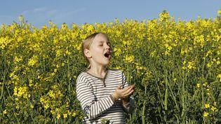 Une jeune fille éternuant à cause des pollens. (LEMOINE / BSIP / AFP)