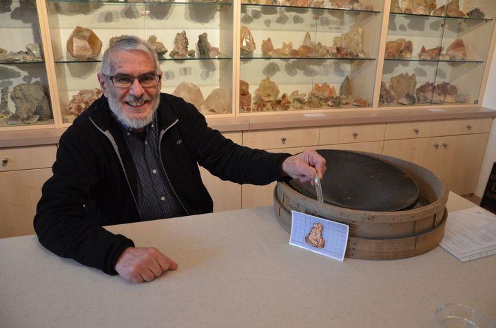 Raphaël Rethoré pose avec quelques paillettes d'or, son matériel d'orpaillage et la photo de la plus grosse pépite (0,5 cm) jamais découverte à Saint-Pierre-Montlimart (Maine-et-Loire), le 15 avril 2015. (THOMAS BAIETTO / FRANCETV INFO)