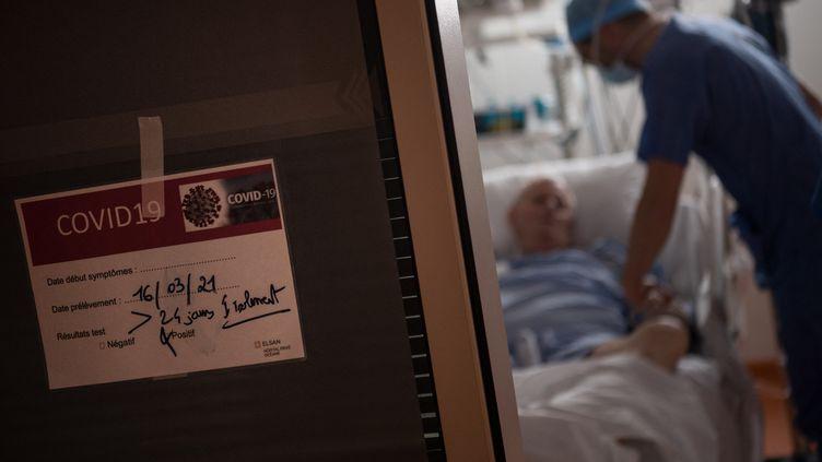 Un soignant s'occupe d'un patient atteint du Covid-19 dans le service de réanimation del'hôpital privé Océane à Vannes (Morbihan), le 20 avril 2021. (LOIC VENANCE / AFP)
