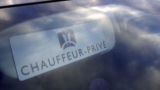 """Affiche """"Chauffeur privé"""" derrière un pare-brise d'un VTC à Paris le 11 février 2016. (AFP)"""