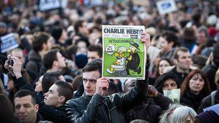 """Un homme brandit un ancien numéro de """"Charlie Hebdo"""", le 11 janvier 2015 à Paris, lors de la """"marche républicaine"""" contre le terrorisme. (EMERIC FOHLEN / NURPHOTO / AFP)"""