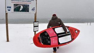 Un surfeur sous la neige, le 28 février 2018, sur la plage de Palavas-les-Flots (Hérault). (PASCAL GUYOT / AFP)