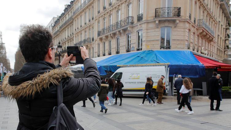 La brasserie Le Fouquet's, vandalisée sur les Champs-Elysées à Paris, samedi 16 mars, est recouverte de bâches, lundi 18 mars 2019. (PHILIPPE WOJAZER / REUTERS)
