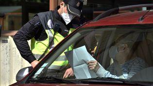 Un policier espagnol contrôle un document de test PCR d'un automobiliste au poste frontière du Perthus (Pyrénées-Orientales), le 30 mars 2021. (RAYMOND ROIG / AFP)