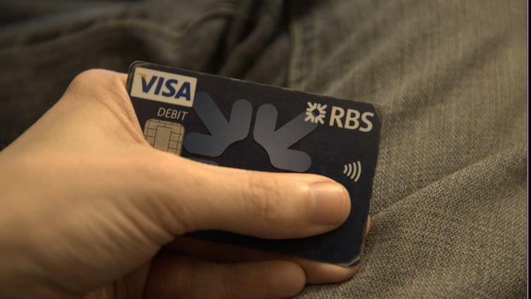 Un client de la Banque royale d'Ecosse tient une carte bancaire Visa, le 25 févier 2015, à Manchester (Royaume-Uni). (JONATHAN NICHOLSON / NURPHOTO / AFP)