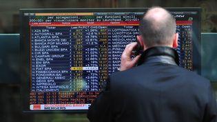 Un homme regarde les cours de la Bourse, à Milan, le 10 novembre 2011. (GIUSEPPE CACACE / AFP)