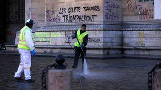 """Des agents de la ville de Paris nettoient l'Arc de triomphe et ses abords, le 2 décembre 2018, au lendemain du rassemblement des """"gilets jaunes"""" sur la place de l'Etoile. (GEOFFROY VAN DER HASSELT / AFP)"""