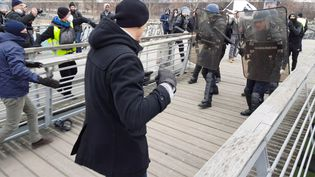 Un homme habillé en noir, de dos, va en découdre avec les forces de l'ordre sur une passerelle enjambant la Seine, à Paris, le 7 janvier 2019. (AFP)