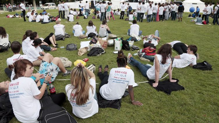 Des jeunes engagés dans le service civique discutent, assis sur la pelouse du Champ-de-Mars, à Paris le 27 juin 2012. (JACQUES DEMARTHON / AFP)