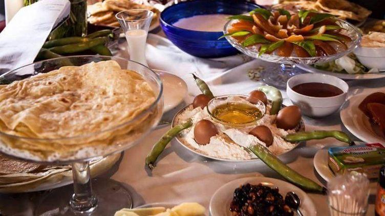 Table de fête sur laquelle trônent terri, farine avec 5 œufs et 5 cosses de fèves fraîches, miel, fruits confits, leben (petit-lait fermenté), levain... (DR capture d'écran)