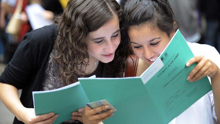 Des élèves de terminale regardent leur livret scolaire, au lycée Chaptal, à Paris. (BERTRAND GUAY / AFP)