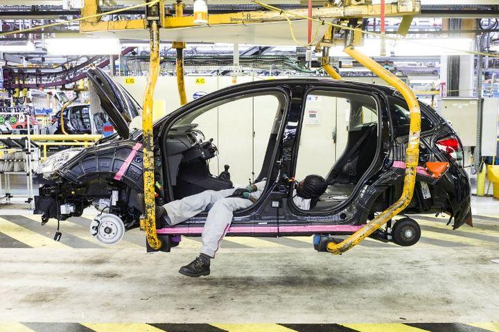 Un intérimaire travaille sur un véhicule dans l'usine PSA Peugeot Citroën d'Aulnay-sous-Bois, en Seine-Saint-Denis, le 10 avril 2013. (FRED DUFOUR / AFP)