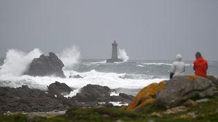 Des personnes regardent la mer agitée devant le phare du Four, dans le Finistère, le 2 novembre 2019. (DAMIEN MEYER / AFP)