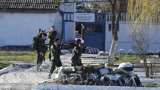 Des soldats ukrainiens emportent des armes, avant de quitter la base de Féodossia (Crimée), dimanche 23 mars 2014. (SHAMIL ZHUMATOV / REUTERS )