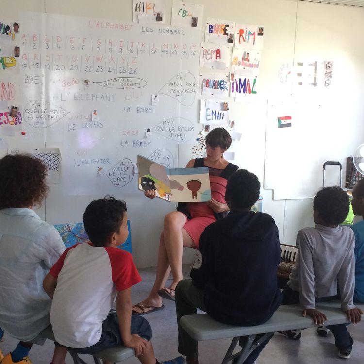 """Constance Calais donne un cours à des enfants migrants, dans une école créée par l'Education nationale, dans la """"jungle"""" de Calais, le 1er septembre 2016. (KOCILA MAKDECHE / FRANCEINFO)"""