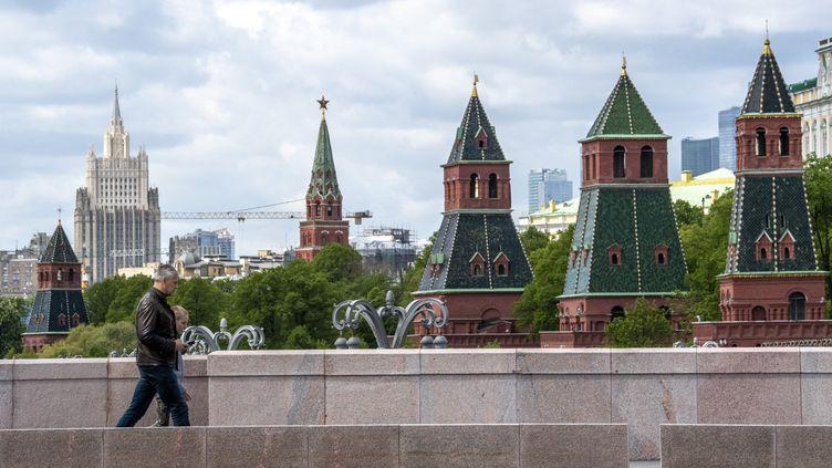 Des personnes traversent un pont avec les tours du Kremlin en arrière-plan dans le centre de Moscou, le 17 mai 2020. Photo d'illustration. (YURI KADOBNOV / AFP)