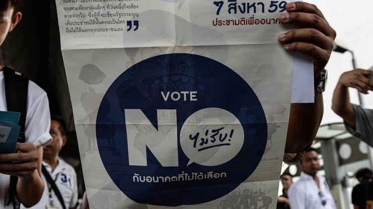 Des militants déploient un tract contre la réforme constitutionnelle à Bangkok, le 16 juillet 2016. (LILLIAN SUWANRUMPHA / AFP)