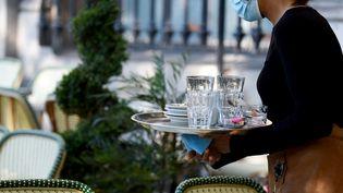 Une serveuse dans un restaurant parisien. Photo d'illustration. (ERIC PIERMONT / AFP)