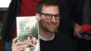 Nicolas Mathieu pose avec son roman, après avoir reçu le prix Goncourt 2018, le 7 novembre 2018. (ERIC FEFERBERG / AFP)