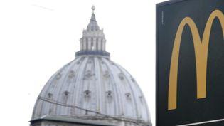 Un panneau indique la direction du McDonald's, non loin de la coupole de la basilique Saint-Pierre de Rome, le 3 janvier 2017  (Tiziana Fabi / AFP)