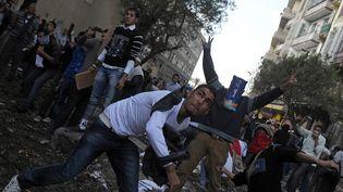 Des manifestants jettent des pierres sur les forces de police, au Caire (Egypte), le 21 novembre 2011. (MOHAMMED HOSSAM / AFP)