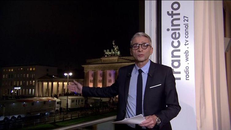 """Jean-François Achili et ses informés en direct de l'ambassade de France en Allemagne, à coté de la porte de Brandebourg, pour cette émission spéciale """"30 ans de la chute du mur de Berlin"""". (FRANCEINFO)"""