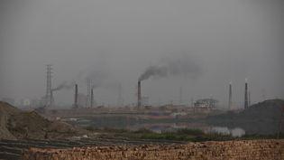 De la fumée s'échappe de cheminées d'un site de fabrication de briques alimenté au charbon, le 19 février 2020, à Dhaka (Bangladesh) (AHMED SALAHUDDIN / NURPHOTO / AFP)
