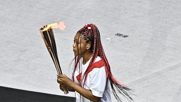 La tenniswoman japonaise Naomi Osaka a été choisie comme dernière relayeuse de la flamme olympique au milieu des athlètes participant à cette cérémonie d'ouverture. Numéro 2 mondiale, elle est une sportive engagée dans des causes comme la lutte contre le racisme. Née d'une mère japonaise et d'un père haïtien, Naomi Osaka est un symbole de la diversité, chère aux valeurs olympiques. (JEFF PACHOUD / AFP)