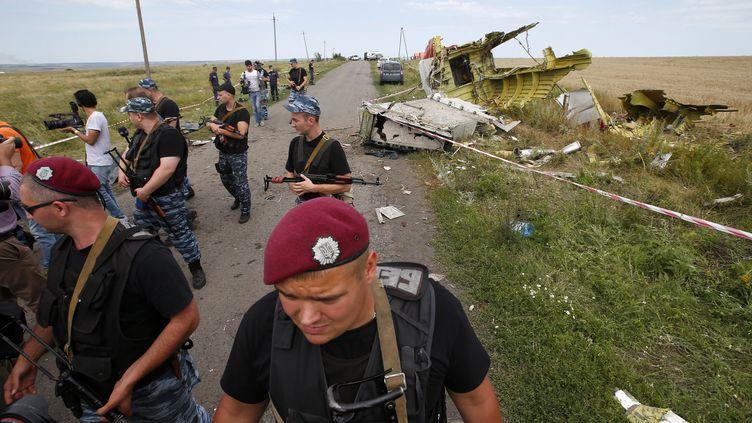 Des rebelles prorusses gardent un des lieux où sont tombés les débris de l'avion de la Malaysia Airlines, crashé dans l'est de l'Ukraine, le 20 juillet 2014. (MAXIM ZMEYEV / REUTERS)
