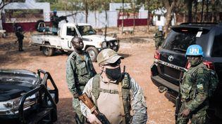 Un casque bleu rwandais aux côtés d'un agent de sécurité privé russe et d'un membre de la garde présidentielle du président centrafricain TouadéraàBangui, le 27 décembre 2020. (ALEXIS HUGUET / AFP)