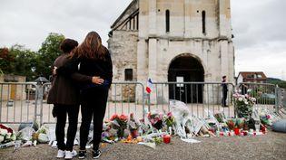 Des anonymes se recueillent devant l'église de Saint-Etienne-du-Rouvray après l'assassinat terroriste du Père Jacques Hamel, le 26 juillet 2016. (CHARLY TRIBALLEAU / AFP)