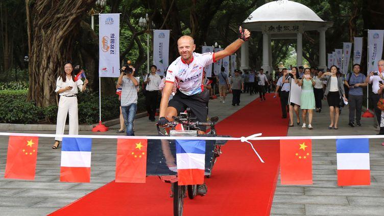 """L'architecte belge Raf van Hulle arrive à Canton (Chine) le 3 août 2018, après avoir parcouru 12 000 km en vélo solaire pour la course """"Sun Trip"""". (AFP)"""