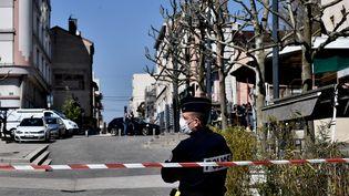 Un policier portant un masque à Romans-sur-Isère (Drôme), sur les lieux de l'attaque, le 4 avril 2020. (JEFF PACHOUD / AFP)