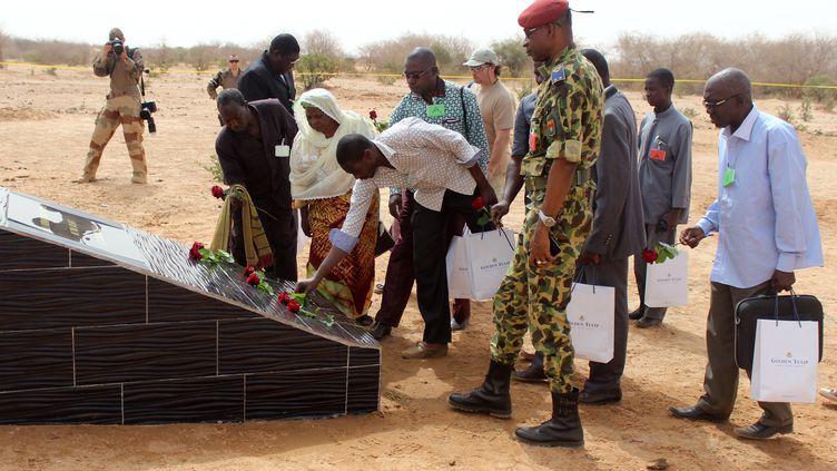 Des familles de victimes déposent des fleurs sur une stèle, près du lieu du crash, le 21 avril 2015, à Gao (Mali). (OLLO HIEN / AFP)