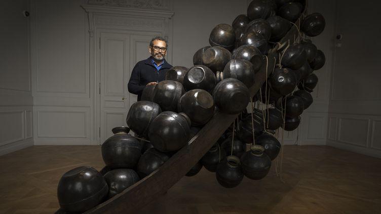 """Subodh Gupta à la Monnaie de Paris, devant une de ses oeuvres (""""Jal Mein Kumbh, Kumbh Mein Jal Hai""""), le 5 avril 2018  (Lionel Bonaventure / AFP)"""