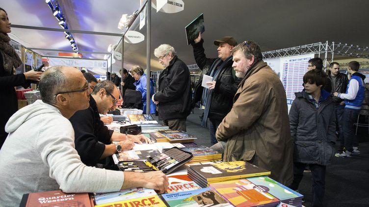 Des dessinateurs dédicacent leur ouvrages lors du festival de BD d'Angoulême (Charente), le 29 janvier 2015. (PIERRE DUFFOUR / AFP)